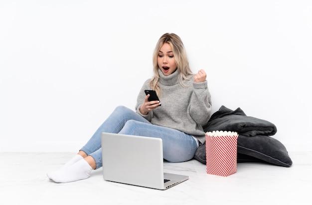 ノートパソコンで映画を見て驚いてメッセージを送信しながらポップコーンを食べて10代の金髪女性