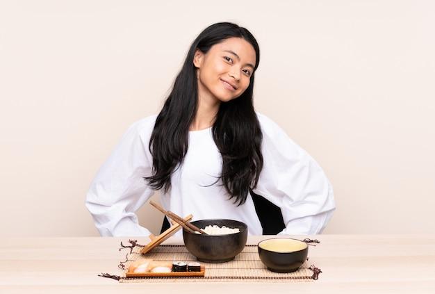 腰に腕でポーズと笑顔のベージュに分離されたアジア料理を食べる10代の女の子