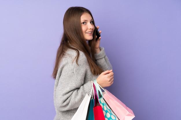 買い物袋を押し、彼女の携帯電話で友達に電話する紫の壁に分離された10代の白人少女