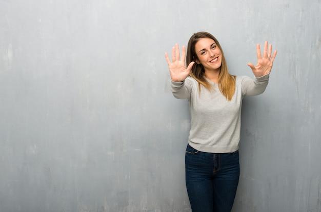 指で10を数える織り目加工の壁に若い女性