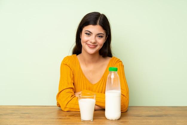彼女の腕を組んで朝食ミルクを持つ10代の女の子
