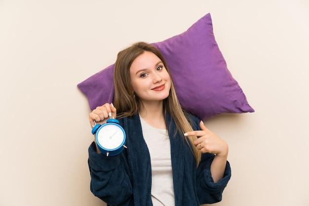ビンテージ時計を保持しているパジャマで10代の女の子
