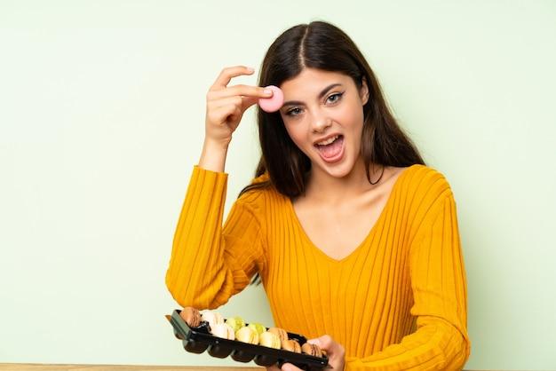 緑の壁の上のマカロンと幸せな10代の女の子