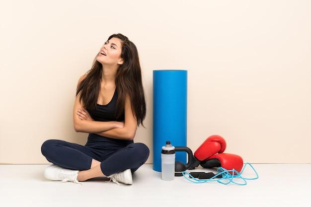 幸せと笑顔の床に座っている10代のスポーツ少女