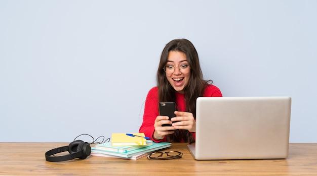 驚いて、メッセージを送信するテーブルで勉強している10代の学生の女の子