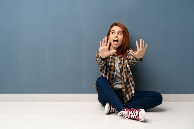 指で10を数える床に座っている若い赤毛の女性