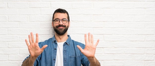 指で10を数える白いレンガの壁の上のひげを持つハンサムな男