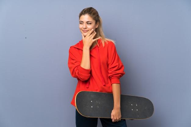アイデアを考えて灰色の壁の上の金髪の10代のスケーターの女の子