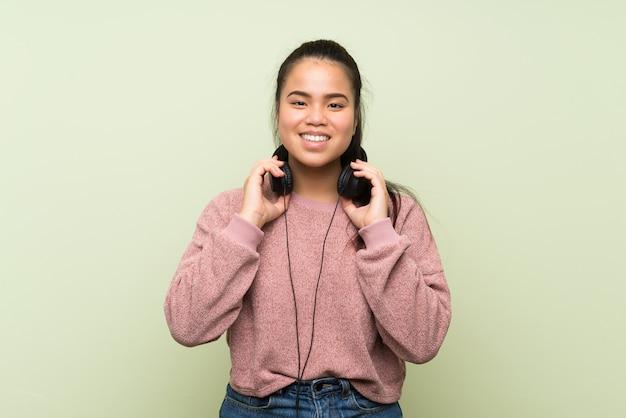 ヘッドフォンで音楽を聴く孤立した緑の壁の上の若い10代のアジアの女の子