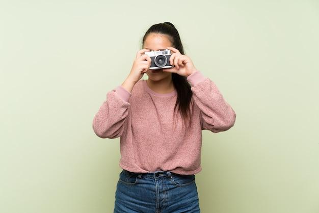 カメラを保持している孤立した緑の壁の上の若い10代のアジアの女の子