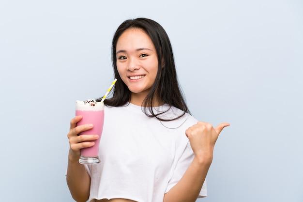 製品を提示する側を指しているイチゴのミルクセーキを保持している10代のアジアの女の子