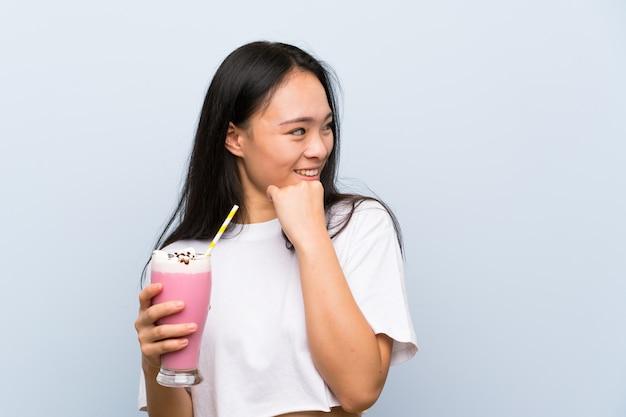 アイデアを考えて、側を見てイチゴのミルクセーキを保持している10代のアジアの女の子