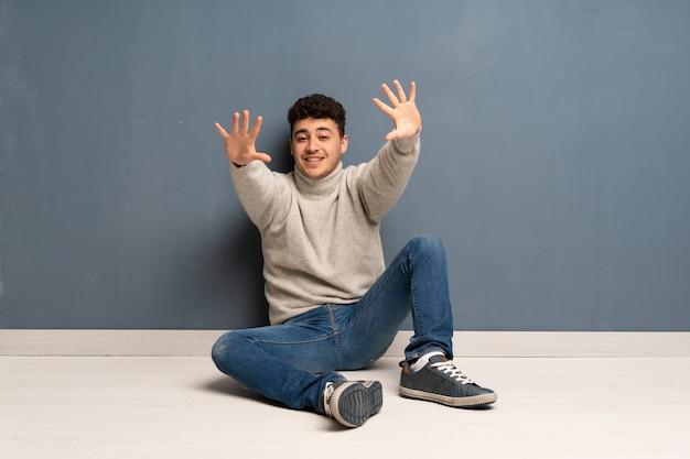 指で10を数える床に座っている若い男
