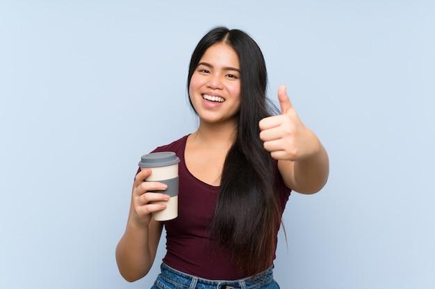 何か良いことが起こったので、親指でテイクアウェイコーヒーを保持している若い10代のアジアの女の子
