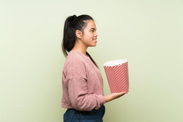 ポップコーンのボウルを保持している孤立した緑の背景の上の若い10代のアジアの女の子