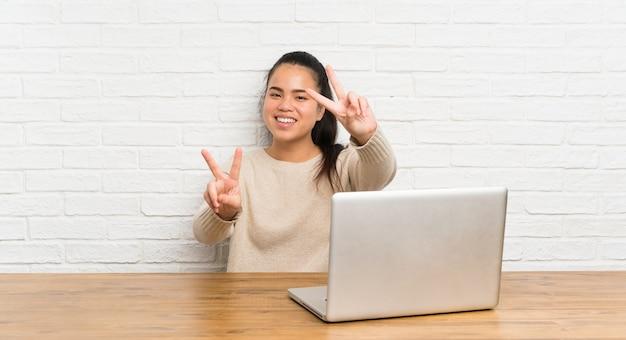笑みを浮かべて、勝利のサインを示すテーブルのラップトップで若い10代のアジアの女の子