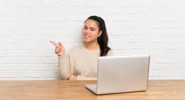側に指を指しているテーブルのラップトップで若い10代のアジアの女の子