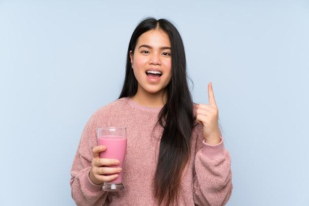 素晴らしいアイデアを指しているいちごのミルクセーキと若い10代のアジアの女の子
