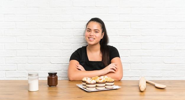 笑ってマフィンケーキたっぷりの若い10代のアジアの女の子