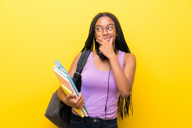 アイデアを考えて孤立した黄色の壁に長い編組髪のアフリカ系アメリカ人の10代学生少女