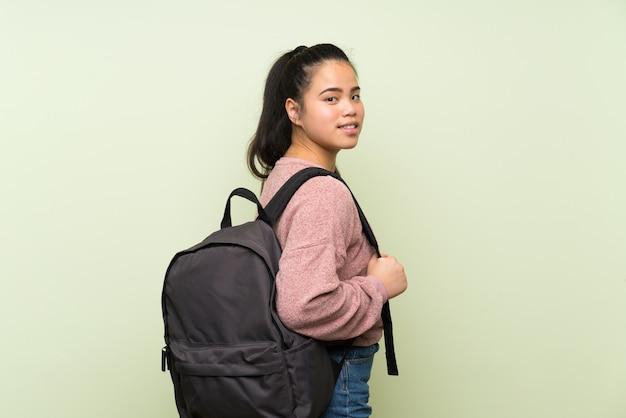 バックパックで孤立した緑の壁の上の若い10代のアジアの女の子