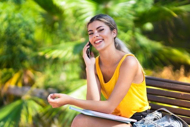 屋外で携帯電話との会話を維持する10代の学生の女の子