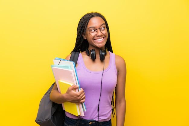 笑って見上げる黄色の壁の上の長い編み髪のアフリカ系アメリカ人の10代学生の女の子