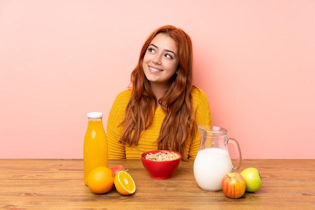 笑って見上げるテーブルで朝食を持っている10代の赤毛の女の子