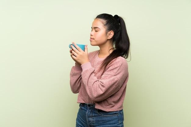 熱い一杯のコーヒーを保持している孤立した緑の壁の上の若い10代のアジアの女の子