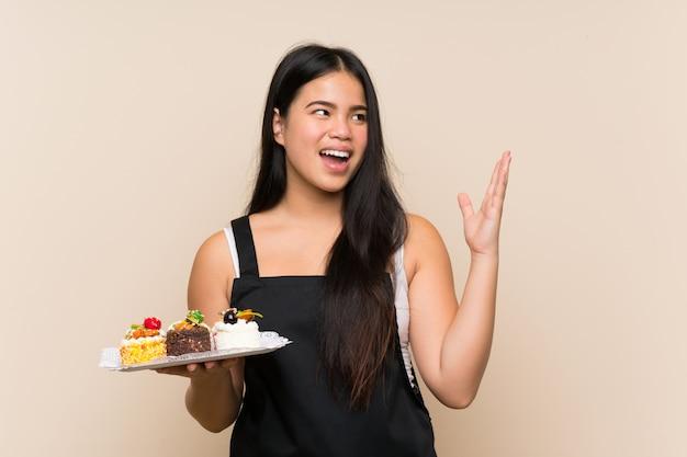 驚きの表情でさまざまなミニケーキをたくさん保持している若い10代の女の子
