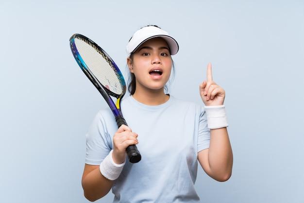 素晴らしいアイデアを指しているテニスをしている若い10代のアジアの女の子