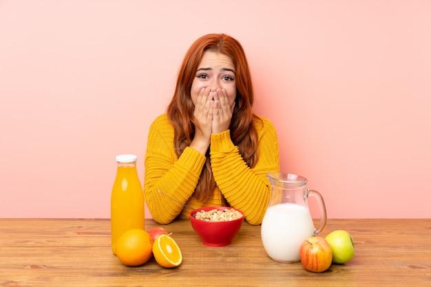 驚きの表情でテーブルで朝食を持っている10代の赤毛の女の子