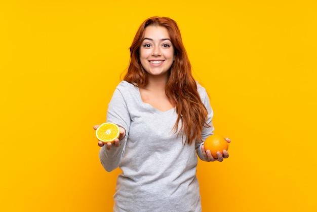 孤立した黄色の背景にオレンジを保持している10代の赤毛の女の子