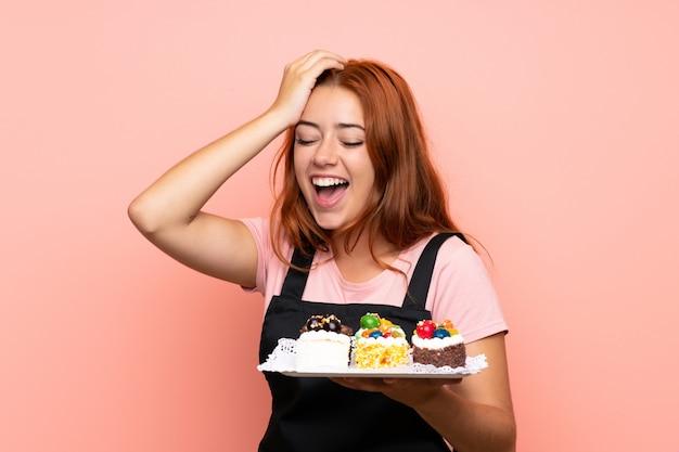 分離されたさまざまなミニケーキの多くを保持している10代の赤毛の女の子が何かを実現し、解決策を意図