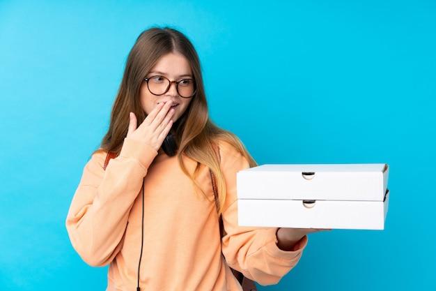 驚きとショックを受けた表情で孤立した青い壁にピザを置く10代の女の子