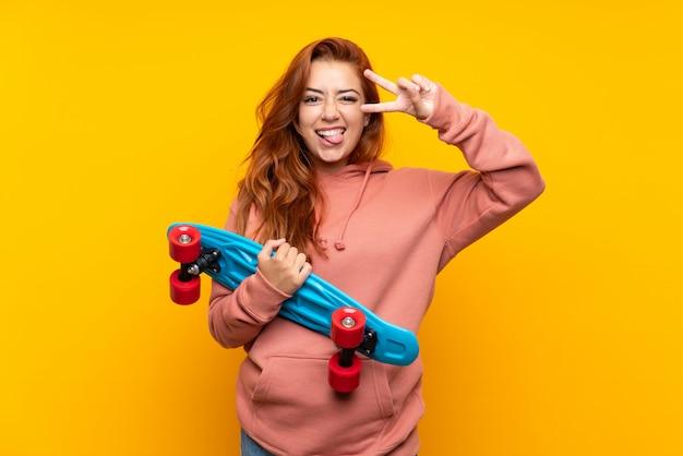 孤立した黄色の上のスケートと10代の赤毛の女の子