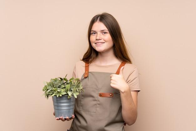 親指ジェスチャーを与える植物を保持しているウクライナの10代の庭師の女の子