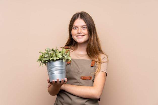 笑っている植物を保持しているウクライナの10代の庭師の女の子