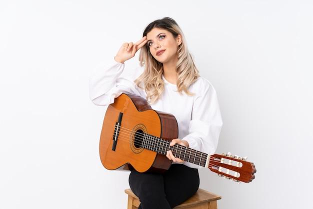 疑いを持つ分離白とギターを混乱させる表情で10代女性