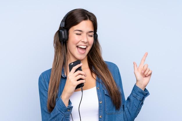音楽を聴くと分離の青い背景に歌っている10代のブラジルの女の子