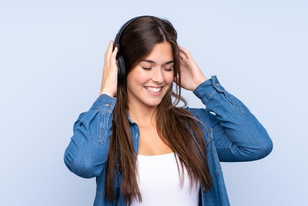 分離の青い背景の上の音楽を聴く10代のブラジルの女の子
