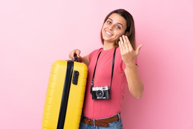 10代の旅行者の女性の手に来るように招待分離のピンクの壁にスーツケースを保持しています。あなたが来て幸せ