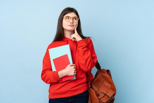 アイデアを考えてサラダを保持している若い10代学生女性