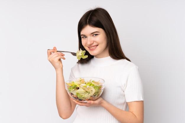 孤立した白い壁にサラダを置く若いウクライナの10代女性