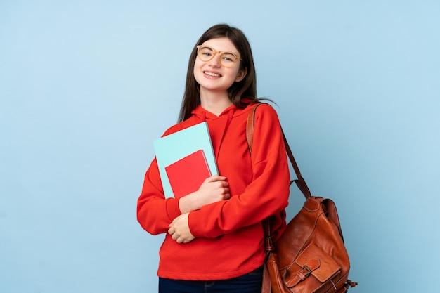 孤立した青い壁の笑いでサラダを保持している若いウクライナ10代学生女性