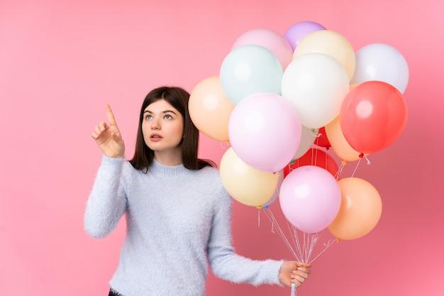 透明なスクリーンに触れる分離のピンクの壁にたくさんの風船を保持している若いウクライナの10代女性