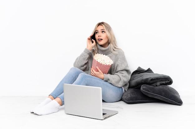 テイクアウトするコーヒーと携帯電話を保持しているラップトップで映画を見ながらポップコーンを食べる10代のブロンドの女の子