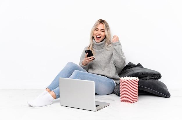勝利の位置に電話でノートパソコンで映画を見ながらポップコーンを食べて10代のブロンドの女の子