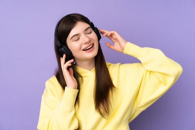 音楽を聴くと歌う紫色の壁の上の若い10代の女の子