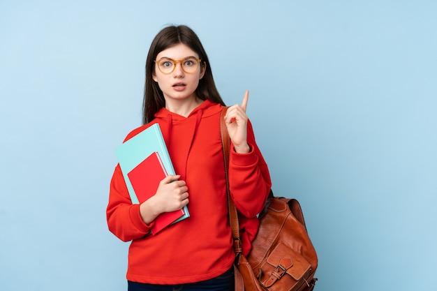 驚いたと側に指を指している青い壁にサラダを保持している若い10代学生の女の子
